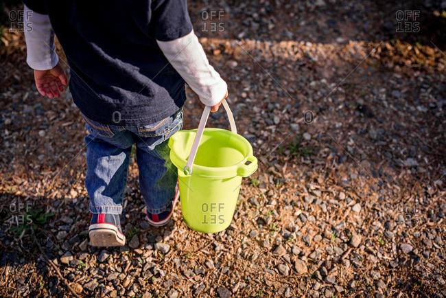 Toddler walking carrying bucket