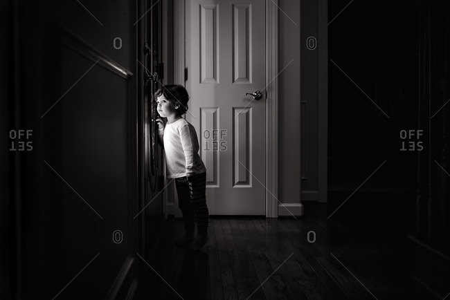 Toddler boy looking through a door