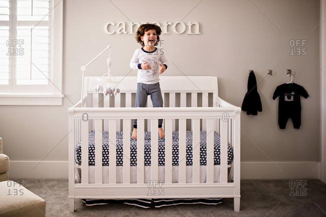 Toddler boy jumping in crib