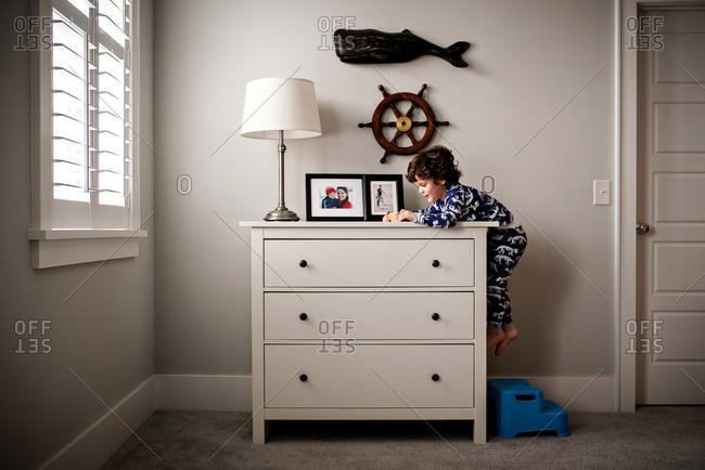 Boy climbing up onto his dresser