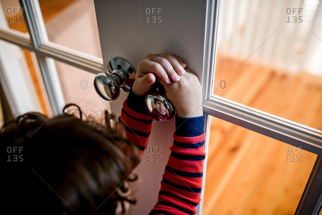Boy looking at reflection in doorknob