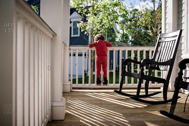 Toddler boy climbing porch railing