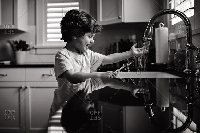 Boy rinsing toothbrush at kitchen sink