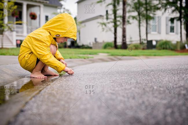 Boy in rain clothes exploring street