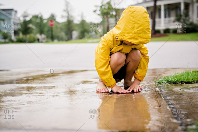 Boy playing in rain water on street