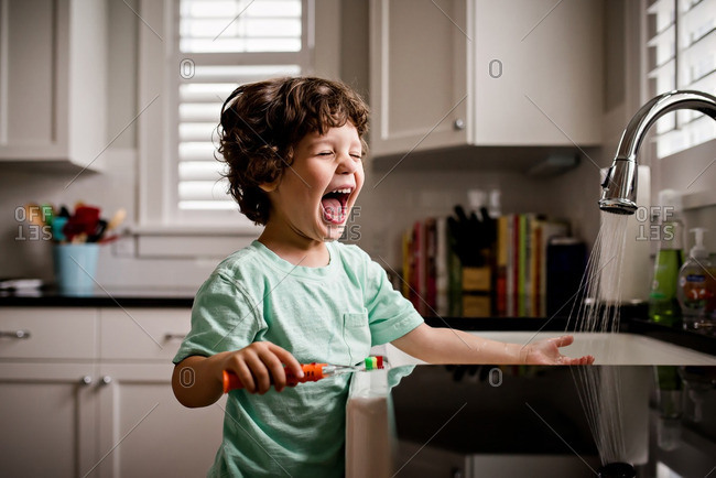 Boy laughing brushing teeth in kitchen