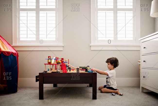 Boy playing with toy cars and track