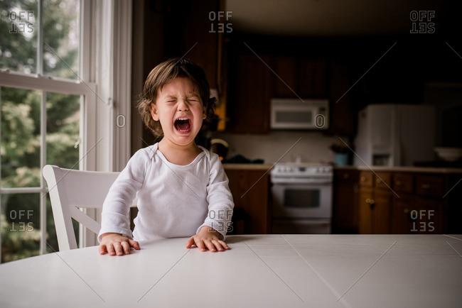 Boy wailing at a table