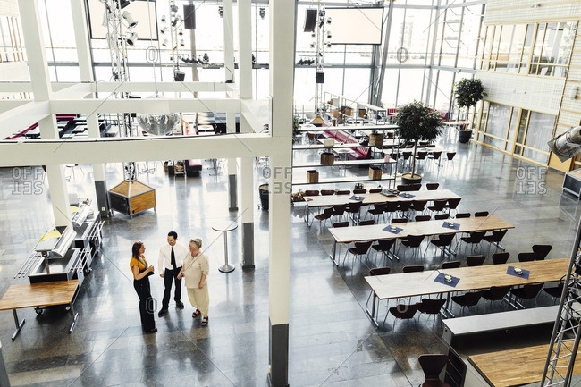 High angle view of colleagues talking in dining hall