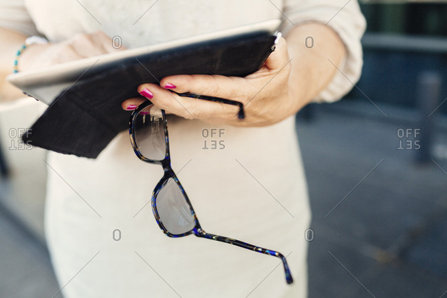 Mid section of mature woman using digital tablet