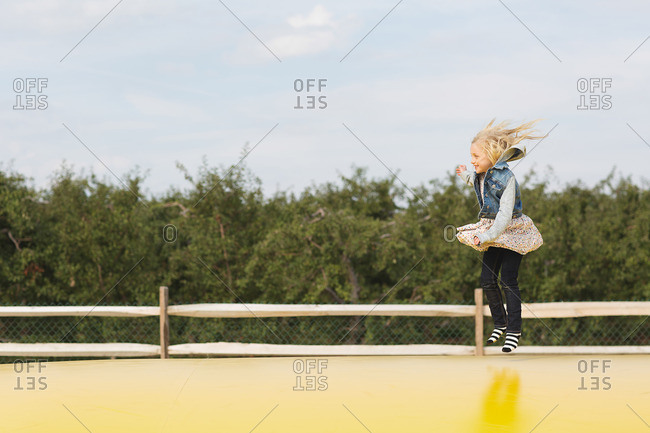 Blonde girl bouncing in midair