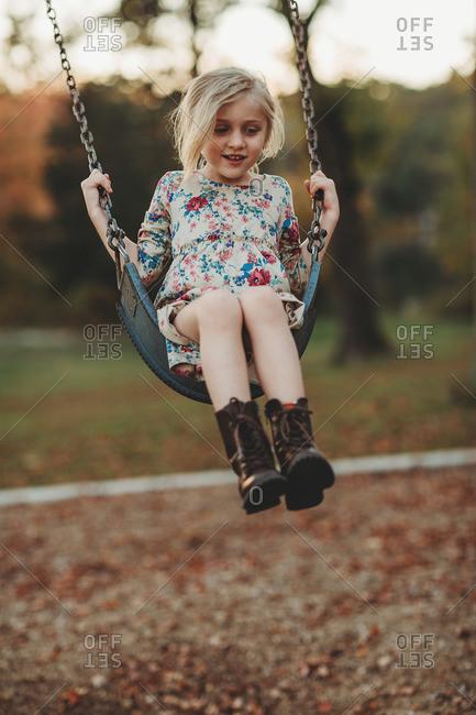 Blonde girl on a swingset