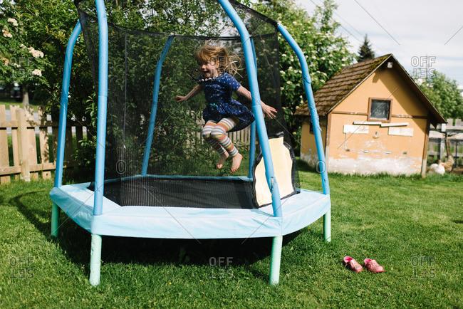 Girl jumping inside a trampoline