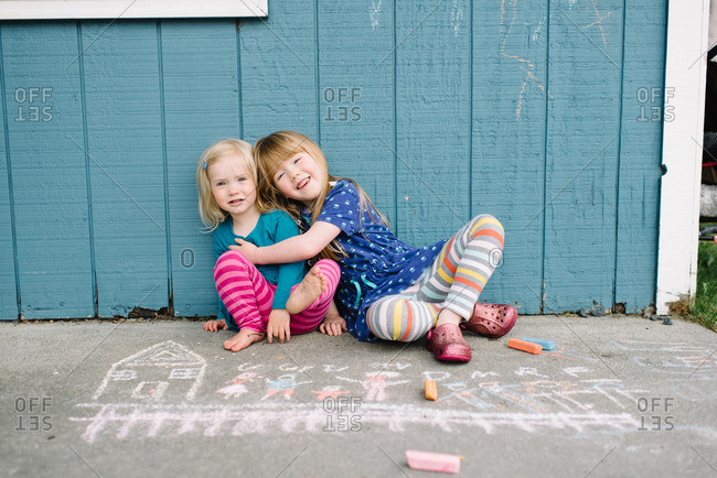 Girls sitting together by chalk drawings