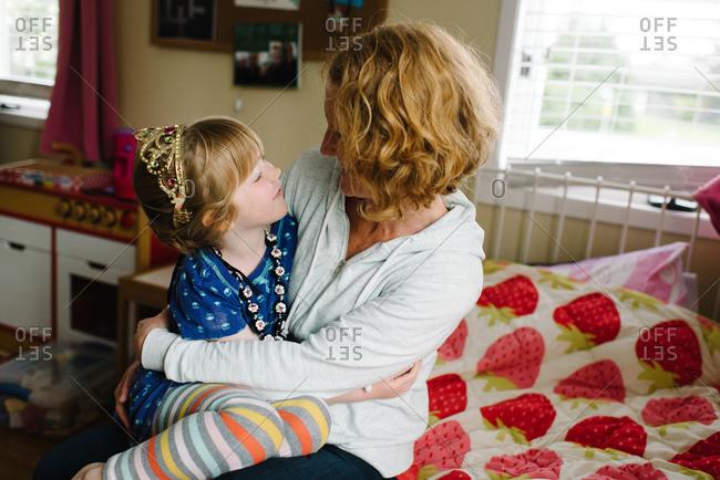 Girl in tiara with loving mom