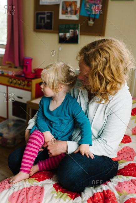 Girl staring off sitting in mom's lap
