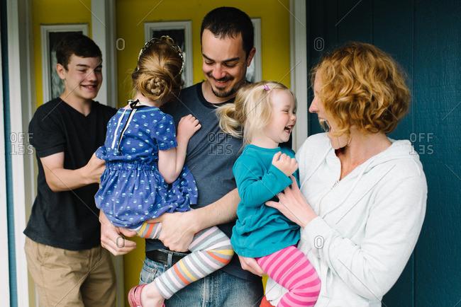 Happy family of five by front door