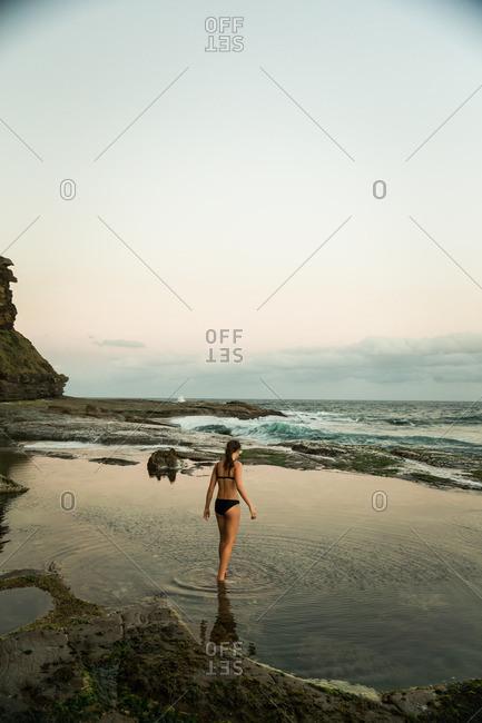 Woman in bikini wading in tide pool