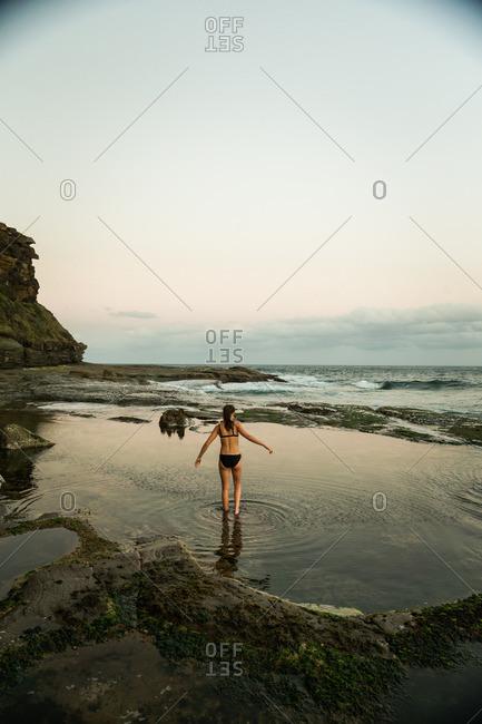 Woman in bikini wading in a tide pool