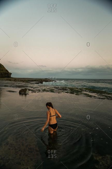 Woman wading in tide pool water