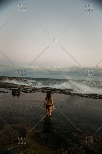 Woman in tide pool watching waves
