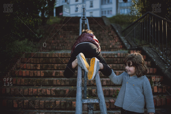 Boy sliding down stair railing outside while sister watches