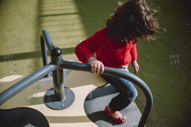 Girl playing on a merry go round at a playground