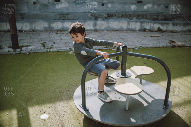 Boy playing on a merry go round at a playground