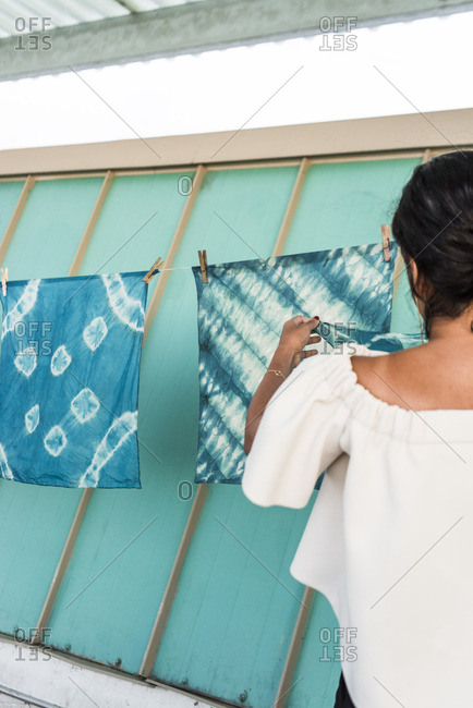 Woman hanging tie-dyed cloth on a line