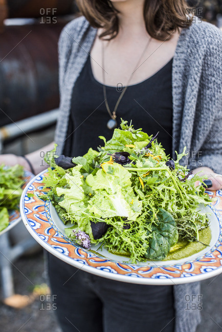 Woman carrying leafy salads