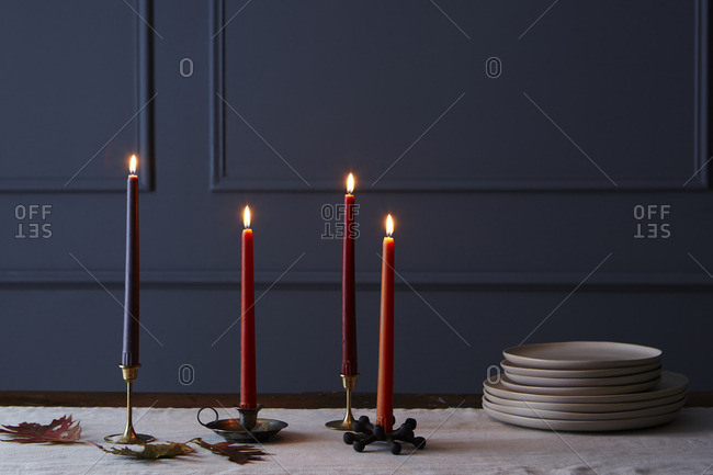 Lit candles on a table with plates and table runner