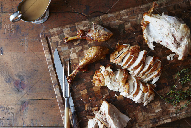 Turkey carved on a wooden cutting board with utensils and gravy sauceboat