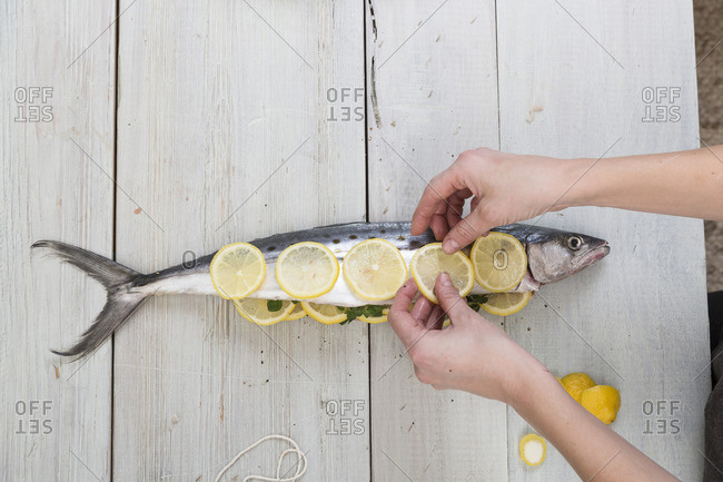 Person placing lemon slices onto a fish