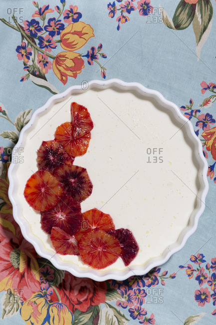 Blood orange dessert in a pie plate on a floral tablecloth