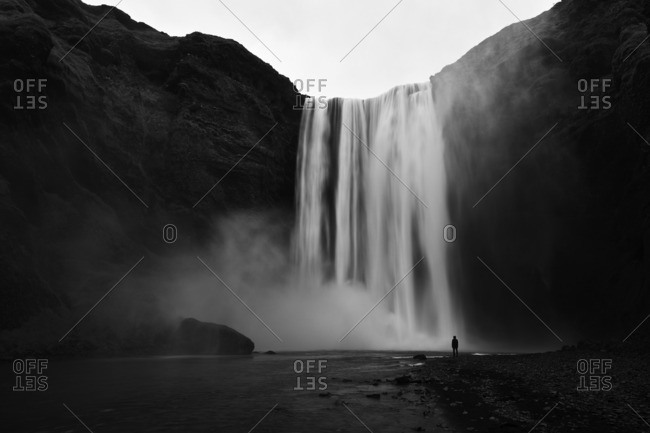 Person silhouetted under waterfall, Iceland