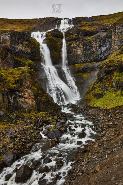 Waterfall cascading down rocky hill, Iceland