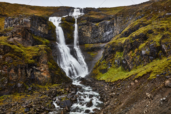 Waterfall flowing down rocky hill, Iceland