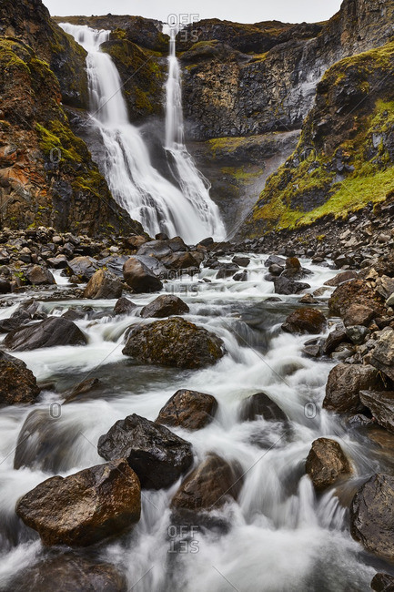 Waterfall down rocky hill in Iceland