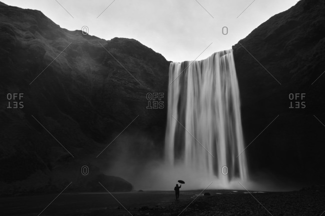 Person with umbrella under waterfall, Iceland