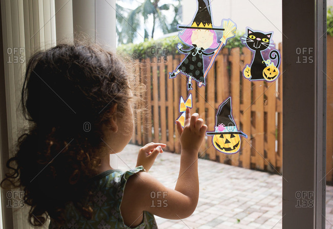Girl putting Halloween decorations on glass