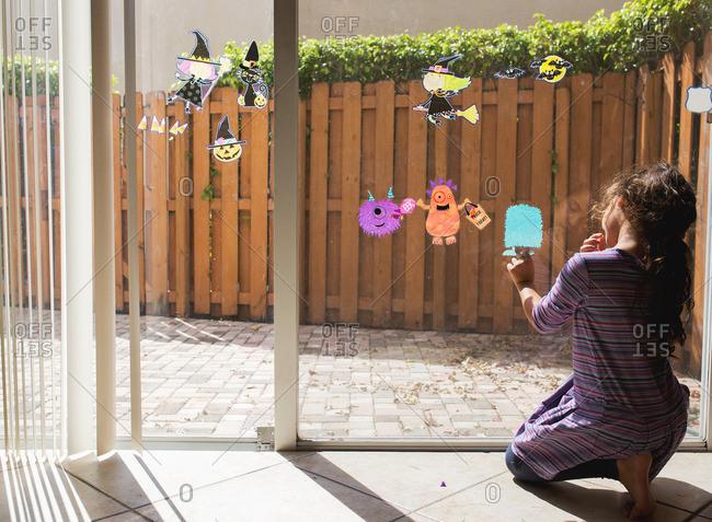 Girl decorating door for Halloween
