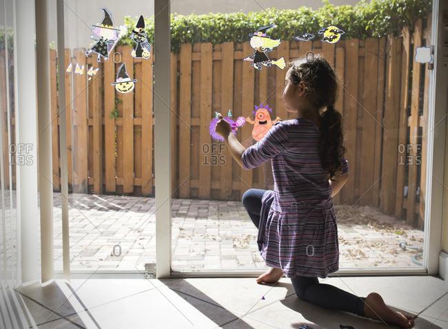 Girl decorating window for Halloween