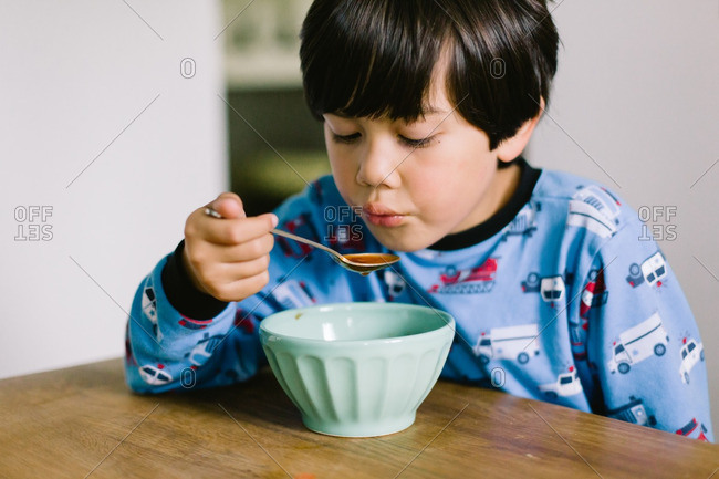 Asian American boy blowing on a spoonful of hot soup