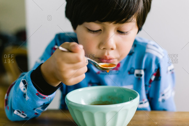 Asian American boy eating a bowl of hot soup