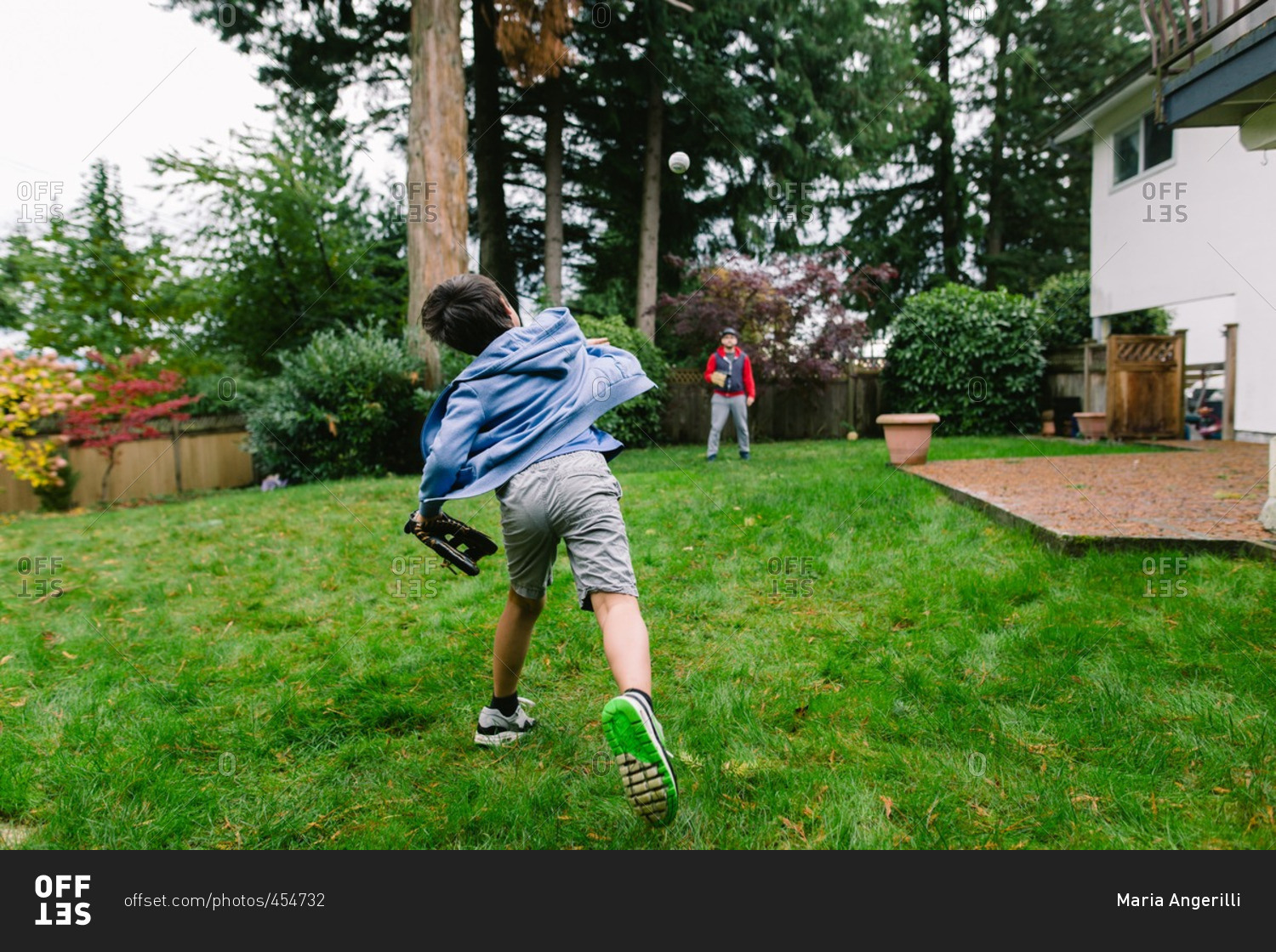 boy playing catch with his dad in the backyard stock photo offset