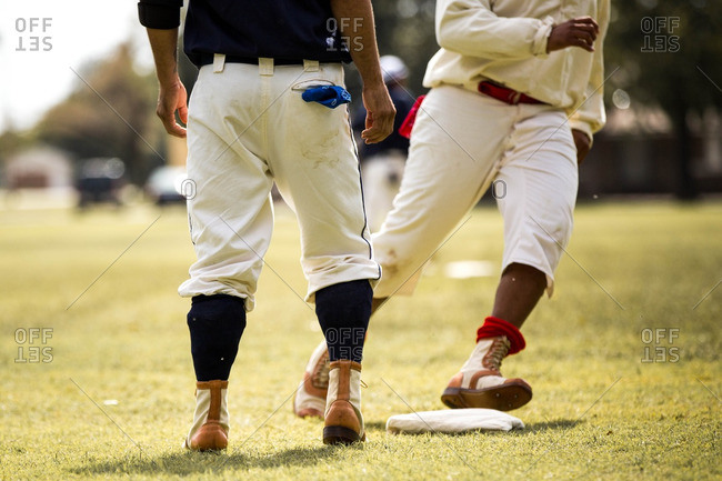 Men playing baseball in old fashioned uniforms