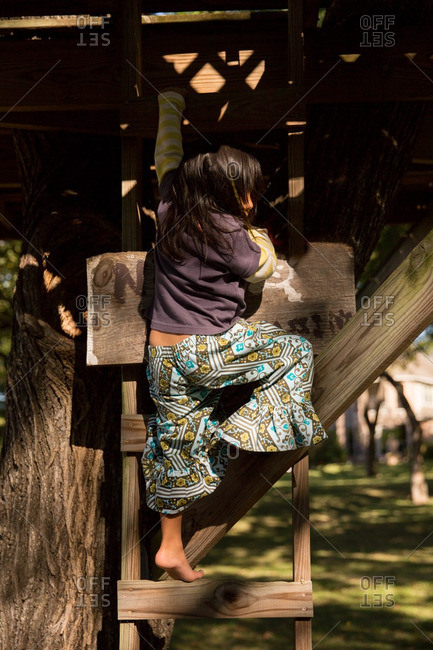 Girl climbing down tree house ladder