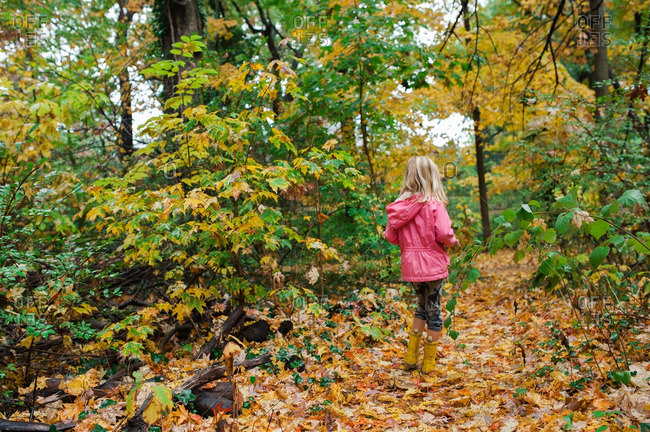 Girl hiking on a trail covered with fallen leaves