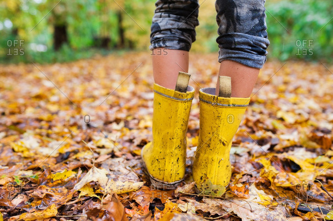Close-up of a girl wearing yellow galoshes while hiking on a trail covered with fallen leaves