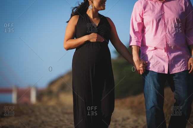Pregnant woman walking holding man's hand